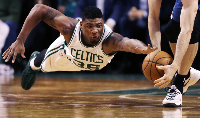 Boston Celtics guard Marcus Smart dives as Minnesota Timberwolves forward Robbie Hummel picks up the loose ball at the Boston Garden.