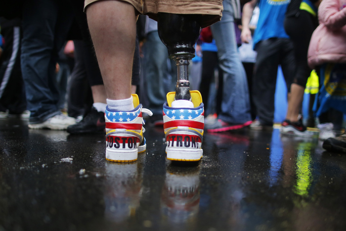 "The shoes of 2013 Boston Marathon bombing survivor J.P. Norden read ""Boston Strong"" as he stands at the finish line on the one-year anniversary of the bombings in Boston, Massachusetts April 15, 2014.  J.P. and his brother Paul, also a bombing survivor, took part in the final portion of the ""Legs for Life Relay"", joining family members and friends who walked the entire Marathon route to raise money for children needing prosthetic limbs."
