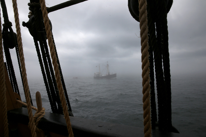 PROVINCETOWN-BOSTON, MA - 7/15/2014: In FOG seen from The Charles W Morgan that sails from Provincetown to Boston is a 1940's eastern rig dragger ROANN also part of Mystic Seaport Museum used as a tender for the voyage. .