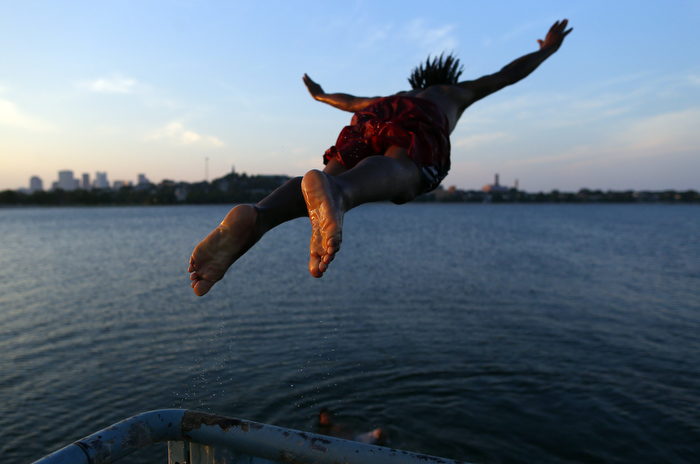 South Boston, Massachusetts -- 07/08/2014--   Edson Pontes, of Dorchester leaps off of a pier into Old Harbor in South Boston, Massachusetts July 8, 2014.