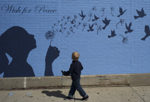 """A boy looks up at a mural reading """"A Wish for Peace"""" in Medford, Massachusetts September 15, 2014."""