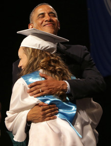 President Obama hugs a graduate during Commencement ceremonies inside the DCU center.  President Obama was the featured guest speaker at Worcester Technical High School's graduation at the DCU Center in Worcester, MA. Worcester Technical High was lauded for transforming from the lowest performing school in the city and one of the lowest performing vocational schools in the state to a 2013 U.S. Department of Education Blue Ribbon School.