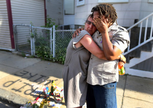 Dorchester- 06/08/14- Michael DePIna, the brother of peace activist Joao DePina was shot in the head and killed Friday night on Taft Street. Joao broke down as he  is comforted by a neighbor in front of a memorial set up at the spot he was shot.