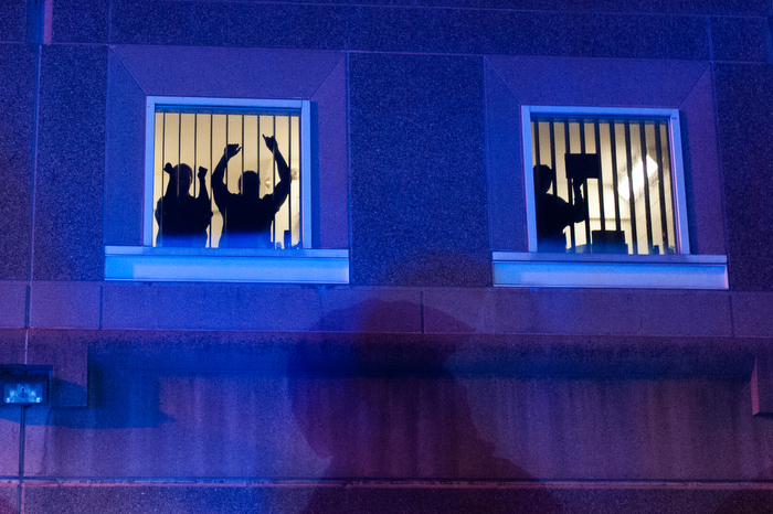 Individuals in the South Bay Correctional Facility animate in their windows during the Indict America rally in Boston on November 25th, 2014.