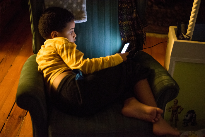Tijan plays on his Nintendo DS while their family hangs out in their Fall River apartment before Whitney and Musa leave for a REAL program dinner in Dowling Hall on Saturday, January 10th, 2015.
