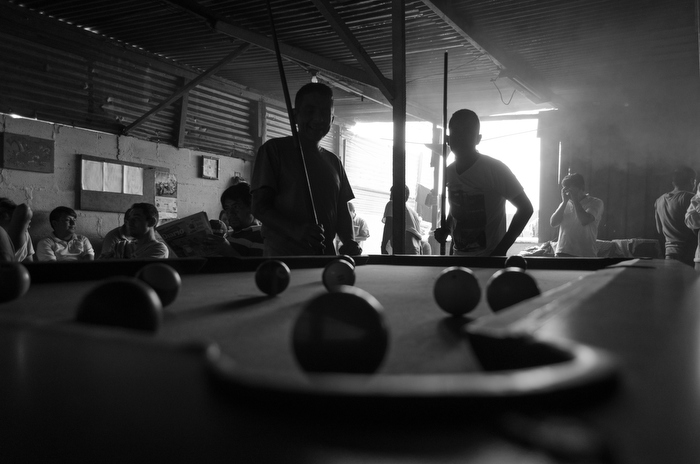 Some members of the program play pool to help pass the time.