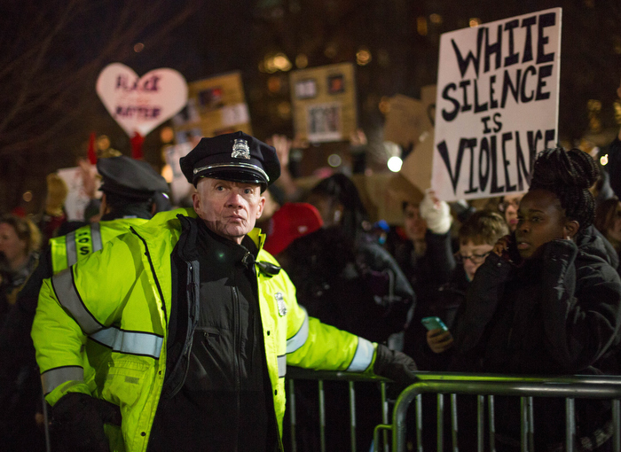 Boston. Dec. 4, 2014. A police officer stands guard at a barricade that prevent protestors from getting close to the tree lighting ceremony at Boston Common on Thursday night.