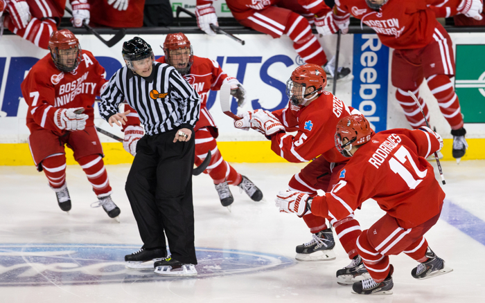 BOSTON, MA - FEBRUARY 23: Linesman Marc Sullivan looks for an escape route as Matt Grzelcyk #5 of the Boston University Terriers celebrates his overtime winning goal against the Northeastern University Huskies with teammates Evan Rodrigues #17, Cason Hohmann #7 and Matt Lane #21 during NCAA hockey in the championship game of the annual Beanpot Hockey Tournament at TD Garden on February 23, 2015 in Boston, Massachusetts.