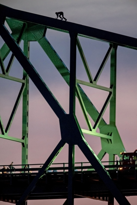 June 10, 2015-Boston,MA. USA.  A man who police say was threatening to jump from Boston's Tobin Bridge, is seen climbing the bridge this evening as a police negotiator, bottom left, speaks to him through a microphone bull horn. The distraught man, who was seen by thousands of evening work commuters, climbed down shortly after sunset, after 2 hours atop the bridge.