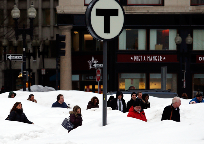 Pedestrians are obscured by snow banks in downtown Boston, Massachusetts February 19, 2015.