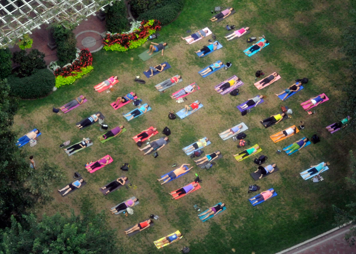 Colorful participants in an evening yoga appear to be taking a nap in a downtown Boston park on Monday, August 31, 2015.