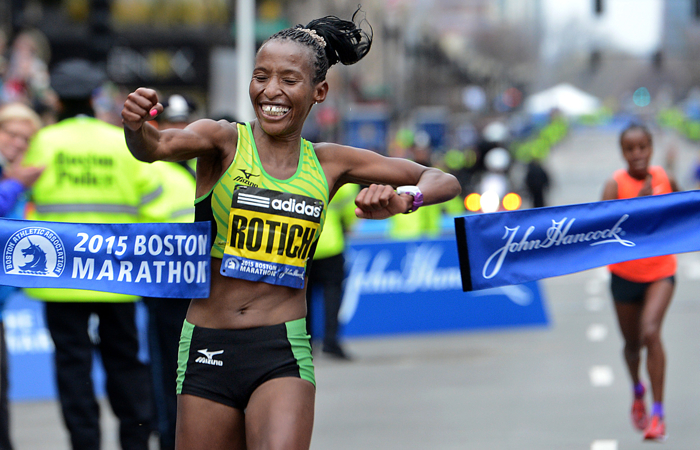 Caroline Rotich of Kenya punches through the tape to win the women's division of the 2015 Boston Marathon.  Mare Dibaba of Ethiopica, right, was just four seconds behind in second place.