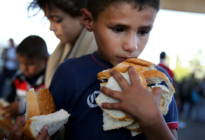 A young boy gathered as much bread as he could hold at an aid station before crossing the Austrian border outside of Hegyeshalom, Hungary. The migrants found a warm welcome from the Red Cross and a group of volunteers from Hungary, Austria and Germany.  The United Nations estimates that more than half of the 4 million Syrian refugees worldwide are women and children. Migrants and refugees from Syria, Afghanistan, and other lands have fled en mass to Europe this year, in search of a better life. Four million refugees have fled Syria alone since a brutal civil war broke out after peaceful prodemocracy protests in 2011.