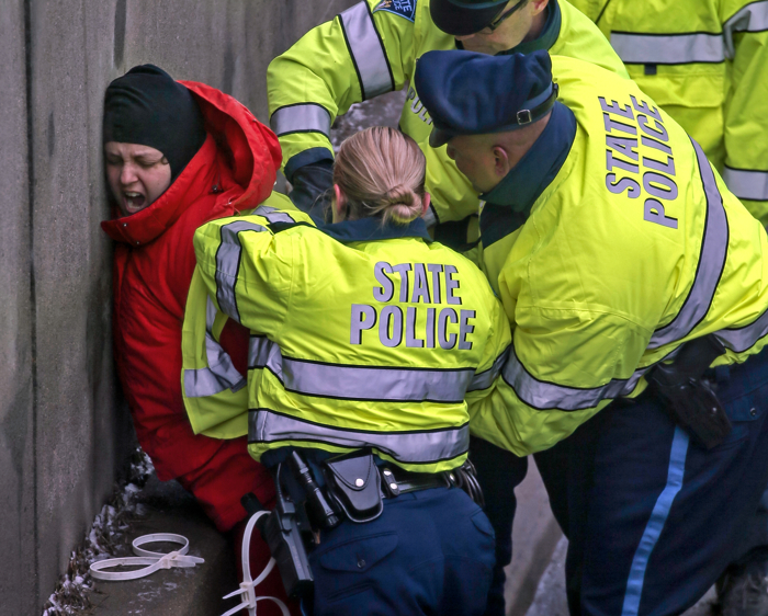01/15/2015-Milton,MA A Black Lives Matter protester is arrested after blocking this morning's commute on route 93 north at East Milton Square. Several people exited  2 vans, laid down in the street as one of their arms, held in place by concrete, affixed to a large barrel. The morning commute was dramatically slowed for 2 hours.