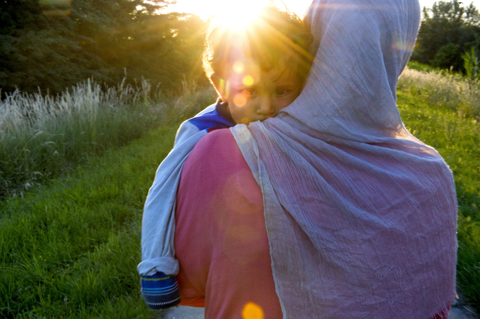 Fatheya carries her son Abdullah while traveling with other Syrian refugees on a path near the Hungarian border on June 2, 2015 in Kanjiža, Serbia. The group walked several miles along the Tisza river at sunset to pass through the border with Hungary at night to avoid the police. Refugees seeking asylum rushed through the Serbo-Hungarian border before Hungary erected a border fence.