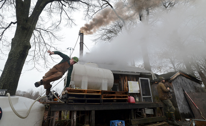 Rusty Varrell, 19, of Holliston, climbs down as steam from the evaporator and smoke from a wood fire pour from the Natick Community Organic Farm sugar shack. After a record slow start to the season, sap finally started to run from maple trees in Natick, Wellesley and Dover in mid-March .  A combination of the heavy layer of snow and cold temperature made  for a very short sugaring season.