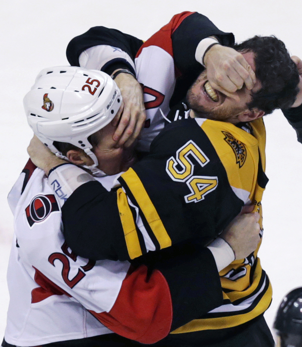 Ottawa Senators right wing Chris Neil and Boston Bruins defenseman Adam McQuaid gouge each other's eyes as they fight.