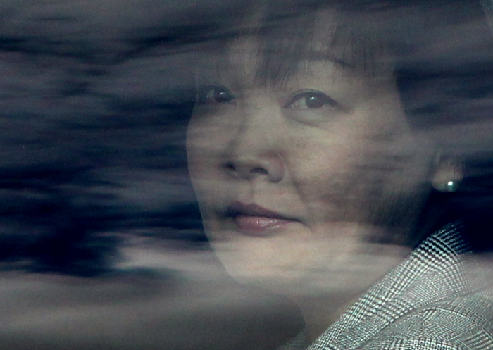 Akie Abe, wife of Japanese Prime Minister Shinzo Abe, is seen through reflections on the window of her limousine just after she and her husband arrived at Logan International Airport in Boston, Mass., Sunday, April 26, 2015. The prime minister and first lady visited the Boston Marathon Bombing site during their trip.