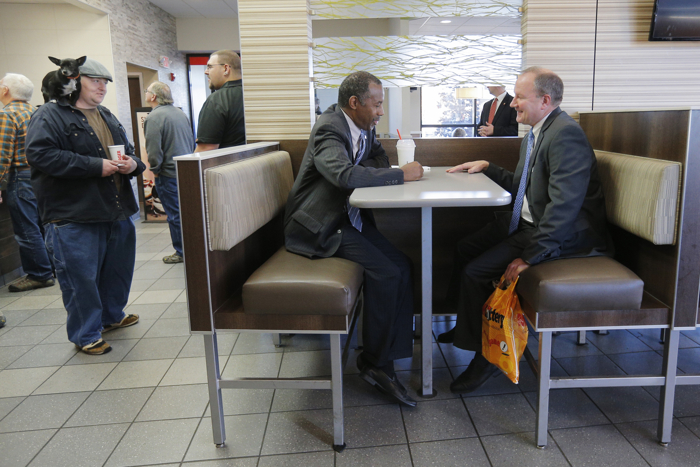 U.S. Republican presidential candidate Dr. Ben Carson (C) waits for his order at a Burger King restaurant in Concord, New Hampshire November 20, 2015.