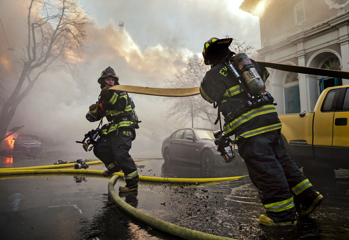 12/03/2016-Cambridge,MA. Everett firefighters, working at the 10 alarm fire in Cambridge, stretch a hose line in the fight to save one of the dozen buildings burning in today's  fire on and around Berkshire street.