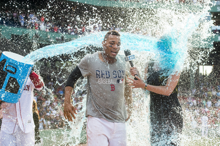 BOSTON, MA - JUNE 23: Xander Bogaerts #2 of the Boston Red Sox and NESN reporter Guerin Austin are doused in Powerade after Bogaerts hit a game-winning single against the Chicago White Sox in the tenth inning on June 23, 16  at Fenway Park in Boston, Massachusetts.