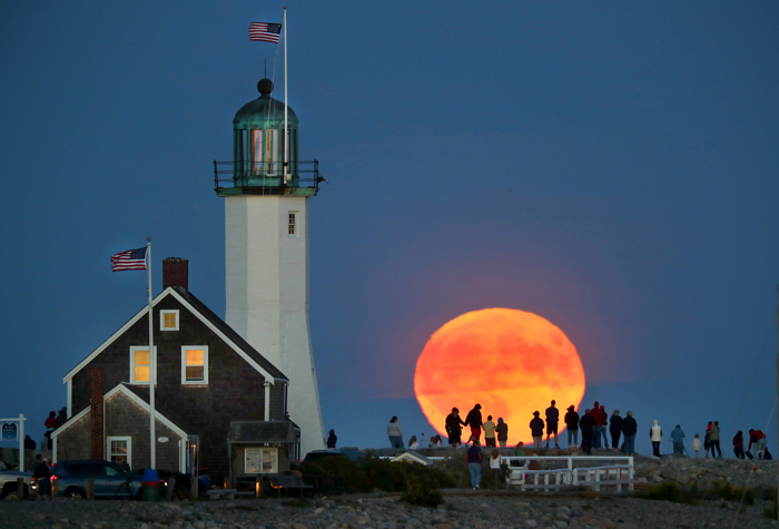 A full harvest moon rises over the ocean as  Scituate Lighthouse rises in the foreground, as a crowd stood on the breakwater next to it  to watch it.