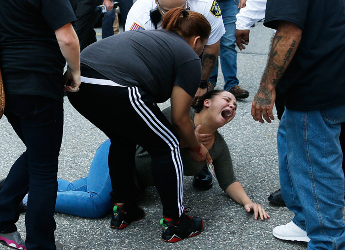 Lawrence, MA -- 9/11/2017 - A woman who was with  family members of an 11-year-old girl who was killed in a hit and run cries out after being knocked to the ground during a chaotic seen which broke out outside of Lawrence District Court following Steven Toro's arraignment.