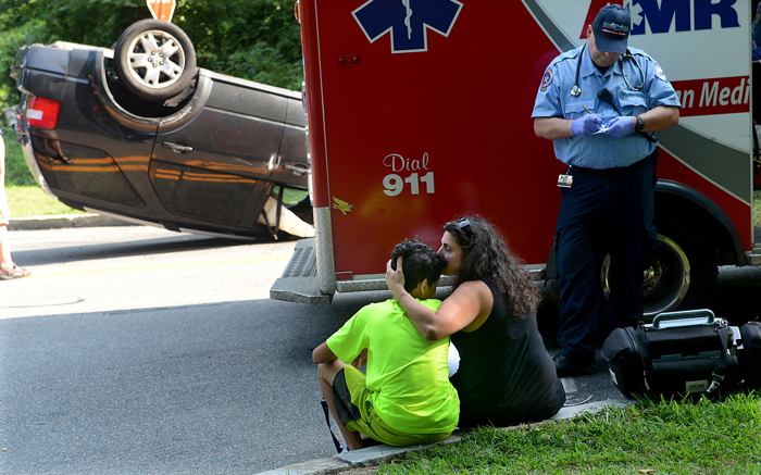 Lilla Martell of Framingham kisses her son, Joseph, 14,  after her Ford Freestyle SUV rolled over following a two-car crash with another SUV at the intersection of Belknap Road and Grove Street in Framingham Wednesday, August 16, 2017.    Martell was taken to an area hospital by ambulance with what appeared to be minor injuries.  Martell's husband, Robert, and son, who were not involved in the crash, came to the scene afterwards.