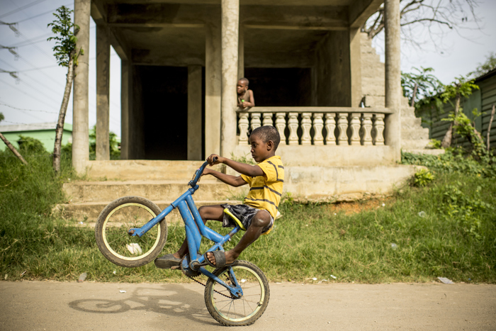 A local boy pops a wheelie on his bicycle in the village of El Mam—n, Dominican Republic Friday, July 21, 2017.