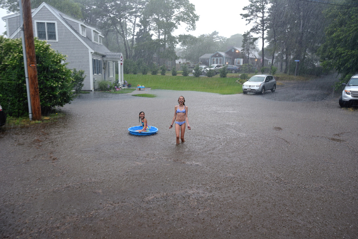 ( West Hyannis Port, MA  07/07/17) Flash flood  on fourth Ave. Sophia Estee, 13 and Eliana Estee 11 play in the torrential rain.  July 07, 2017