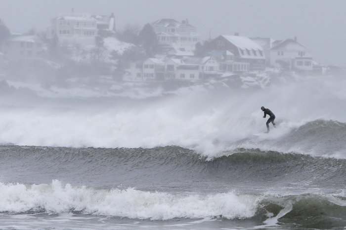 Surfers take advantage of wind and waves from a winter snow storm in Gloucester, Massachusetts, U.S. February 13, 2017.