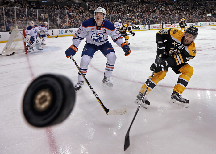 Edmonton Oilers center Ryan Nugent-Hopkins and Boston Bruins center Dominic Moore keep an eye on the puck during the first period of the NHL game at the TD Garden